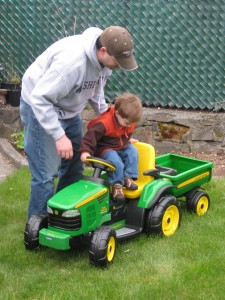 Daddy helping Finley onto the tractor.