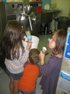 Squeezing in to see the ice cream come out of the machine